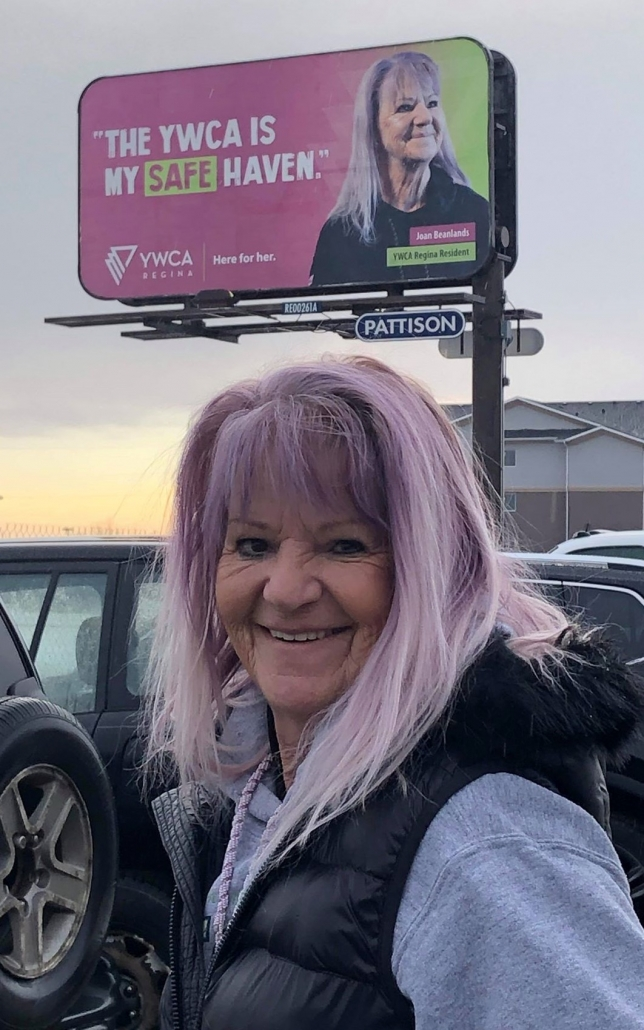 Joan Beanlands poses in front of a YWCA Regina billboard with her picture